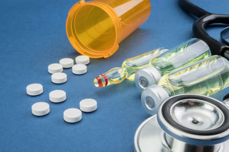 stethoscope, pills, vials in medical room on blue background