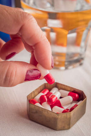 metalic: Hand women take capsules red and white in a pillbox metalic old
