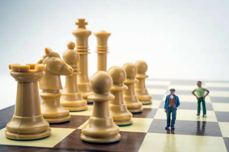 Men thumbnail within a game of chess, concept Imagens