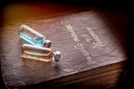 Two vials of medicine on an ancient book of Anatomy of the nervous system, conceptual image Stock Photo