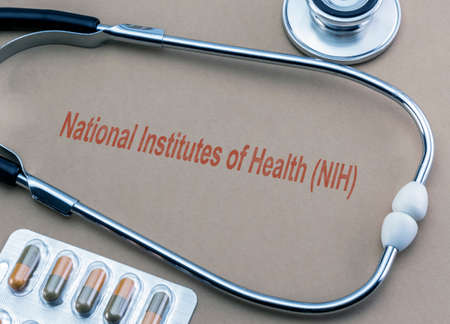 Stethoscope and capsules, digital composition with the text National Institutes of Health (NIH), conceptual image Imagens