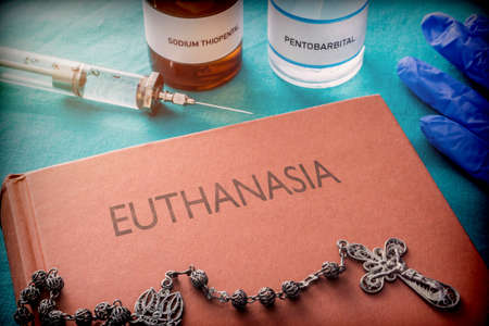 Vintage syringe and drugs used in lethal injection on a book of euthanasia, digital composition, conceptual image Foto de archivo