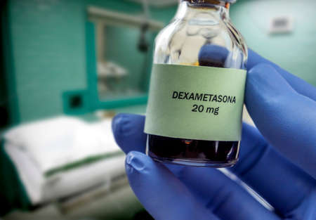 Doctor holds vial of dexamethasone in an operating theater, conceptual image