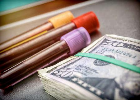 Viales muestra sangre junto con billetes americanos, imagen conceptual sobre copago sanitario