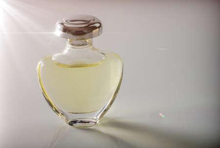 Bottle vintage of perfume illuminated laterally, conceptual image