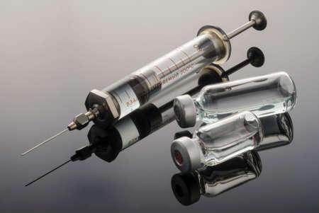 Vintage syringe with vials, conceptual image