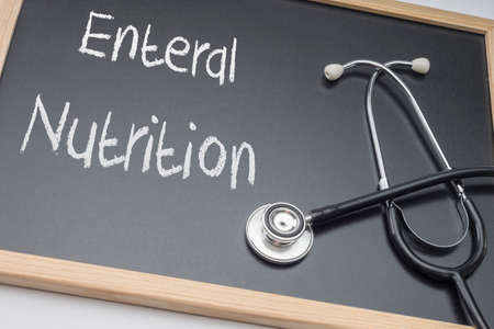Enteral nutrition written on a blackboard, conceptual image, horizontal composition Banco de Imagens