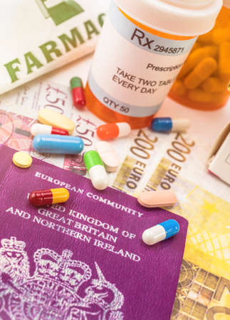 British passport along with several bottles of medicines, concept of medical increase in the crisis of the brexit, conceptual image, horizontal composition