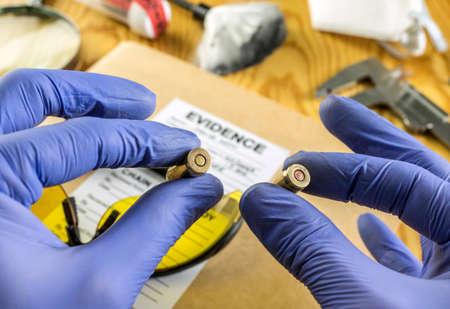Oficial de policía experto comparando dos balas de nueve milímetros en laboratorio de balística Foto de archivo