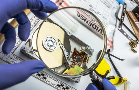 Police expert examines with magnifying glass hard drive in search of evidence, conceptual image Stock Photo