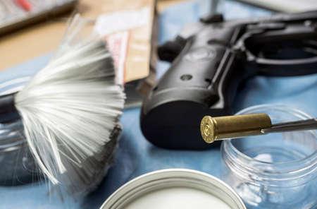 Bullet cap along with a gun in ballistic laboratory, conceptual image