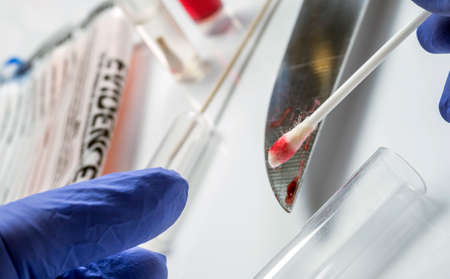Expert police extracts traces of blood on a knife in scientific laboratory