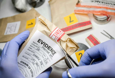 Scientific police opens with scissors a bag of evidence of a crime in scientific laboratory Standard-Bild