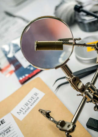 Expert police examines a bullet cap in scientific laboratory with magnifying glass