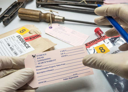 Police expert writes about label evidence number, Various laboratory tests forensic equipment, conceptual image