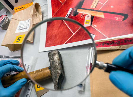 Police scientist analyses hammer from crime scene at laboratory criminologist Stock Photo