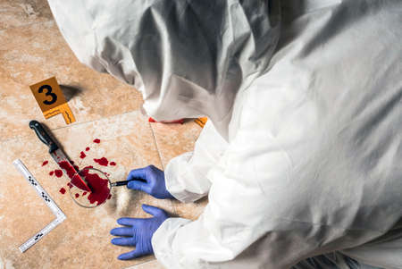Expert Police examining with magnifying glass a knife with blood at the scene of a crime, conceptual image Imagens