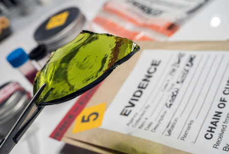 Police expert gets blood sample from glass bottle in Criminalistic Lab Imagens