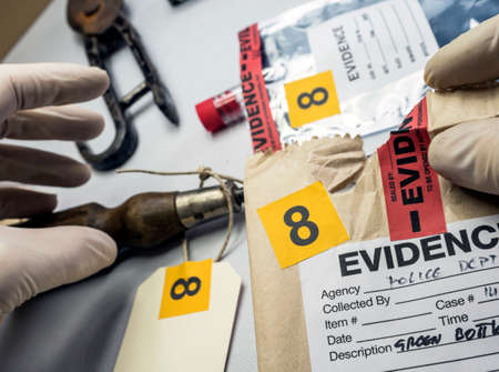 Police expert inspects a screwdriver from the scene of a crime, conceptual image Imagens