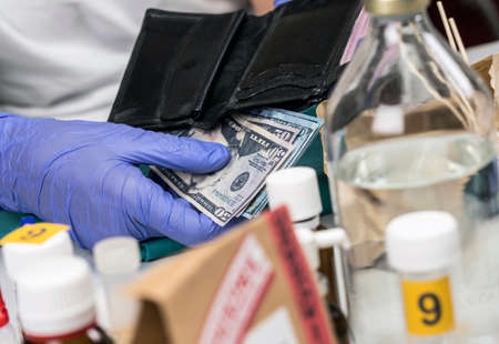 Police specialist examines wallet with money from a crime scene, conceptual image