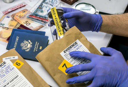 Expert police officer examining American passport of a evidence bag in laboratory of criminology, conceptual image Archivio Fotografico