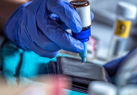 Police specialist examines wallet to collate DNA in a crime scene, conceptual image
