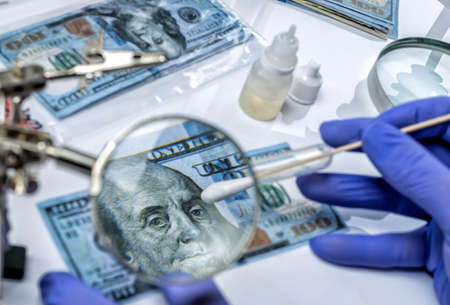 Police scientist investigates fake dollar bills and passports in criminal investigation unit, conceptual image Banco de Imagens