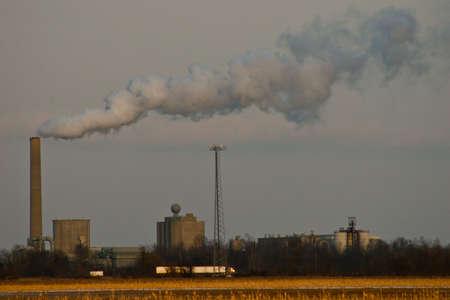 Veld en fabrieks erachter met rook stack