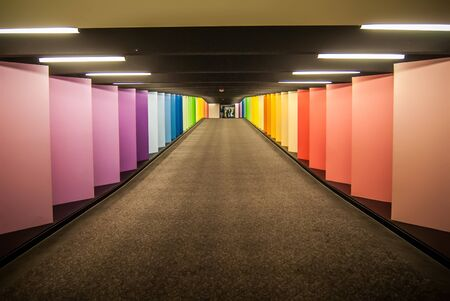 vanishing point of rainbow colored corridor at certain mall Stock Photo