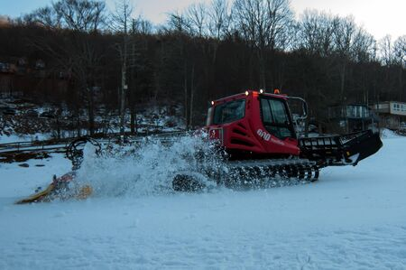 snow grooming machine: snow grooming machine at work smoothing out ski slope for skiing