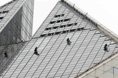 man cleaning windows on a high rise building photo