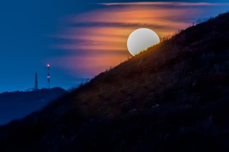 Moon shining bright behind black mountains Stock Photo