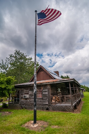 old log cabin and american flag flying over on a pole photo