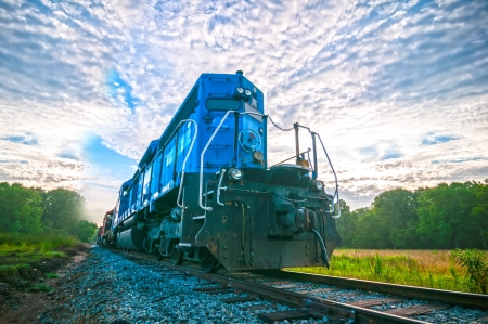 railroad transportation: blue freight train engine at sunrise