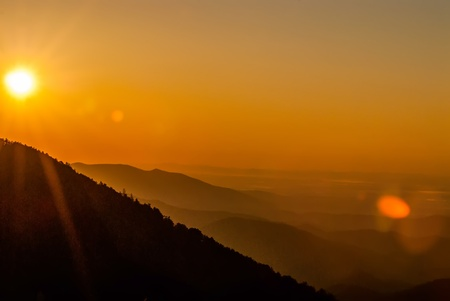 ridgeline: Sun rising over snowy mountains of Smokies in early spring with fog in valleys