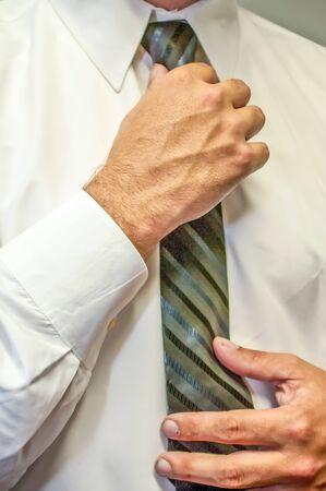 exacting: man fixing a tie with hands in white shirt Stock Photo