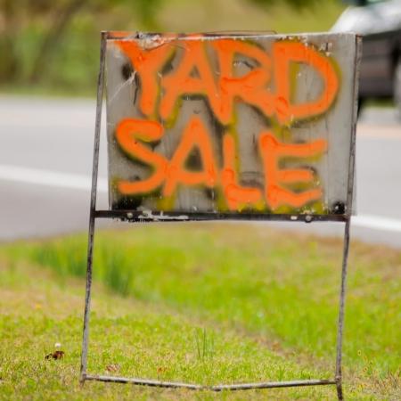 orange handwriting yard sale sign on side of orad