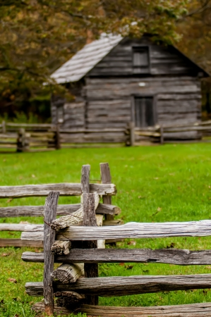 Beautiful Autumn scene showing rustic old log cabin surrounded by split rail fence photo
