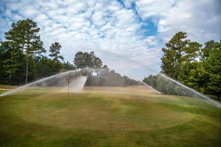 sprinklers: watering green grass lawn on golf course