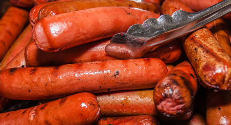 grill tongs sausage: cooked and ready to eat beef frank hot dogs Stock Photo