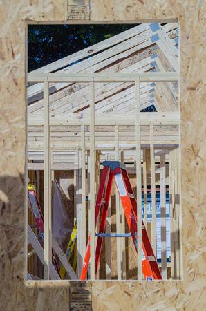 housebuilding: wood frame construction job seen trhough window opening