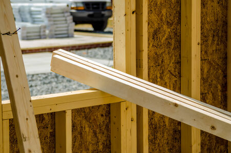 stack of wood stud planks at construction site resting on window opening photo