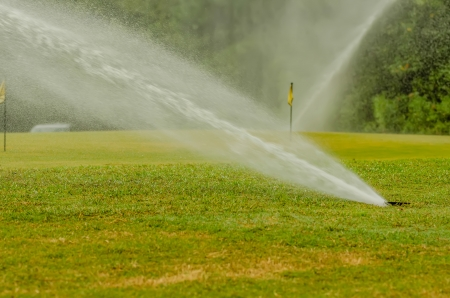 watering green grass lawn on golf course photo
