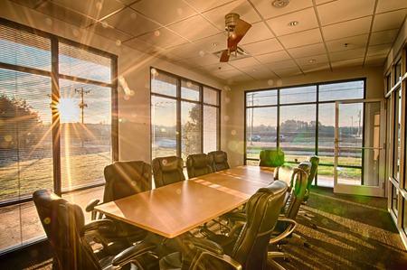 well lit conference room with sun rays shining through 新聞圖片