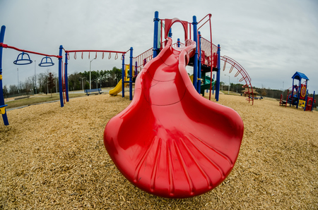at a playground with a red slide in fall