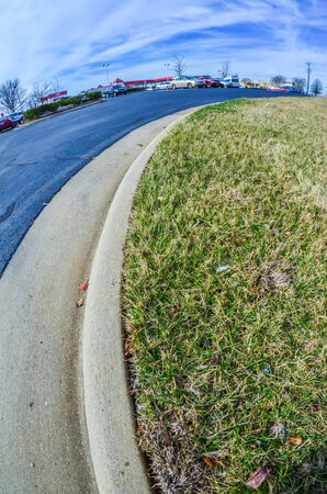 road curb with grass lawn and pavement in a city