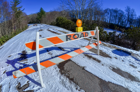 hardwoods: road block set up before snowy and icy road in mountains Stock Photo