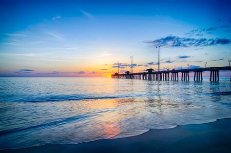 太陽が昇る雲の切れ間からピークし、ノースカロライナ州のアウターバンクスにナグス ヘッド釣り桟橋で波に反映されます。