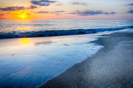 De rijzende zon gluurt door de wolken en komt tot uiting in golven door de Nags Head vissteiger op de buitenste oevers van North Carolina