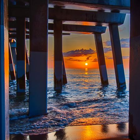 The rising sun peeks through clouds and is reflected in waves by the Nags Head fishing pier on the outer banks of North Carolina